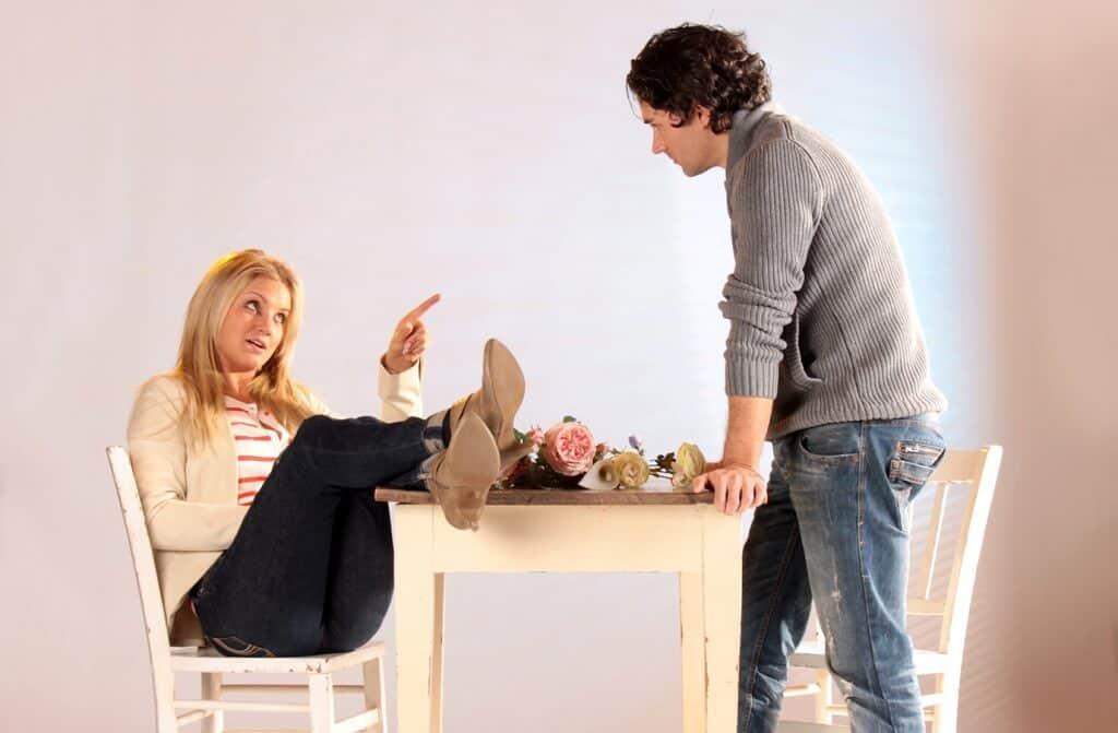 Frau hat ihre Beine auf dem Tisch und zeigt mit erhobenem Finger auf Mann der auf dem Tisch lehnt