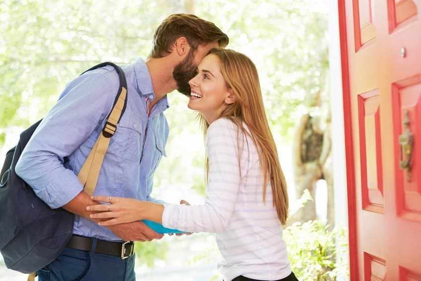 Mann flüstert in das Ohr einer glücklichen Frau