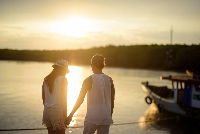 Frau und Mann stehen an einem See die Sonne geht unter und ein Boot ist zu sehen
