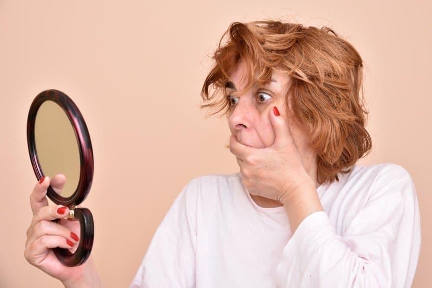 Frau die in einen Handspiegel schaut und sich die Hand vor den Mund hält weil sie erschreckt ist