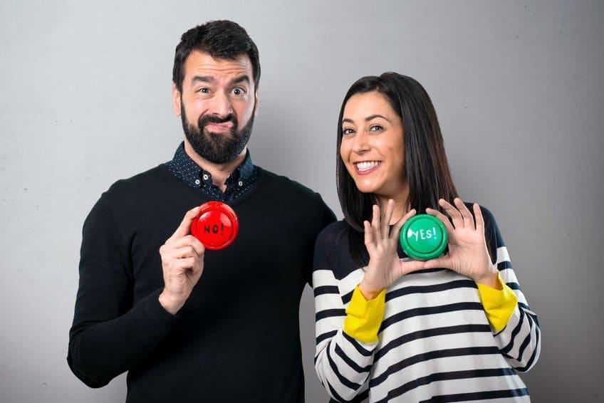 Ein ablehnender Mann der einen roten Button hochhält mit No drauf und eine glückliche Frau die einen grünen Button hochhält mit Yes darauf