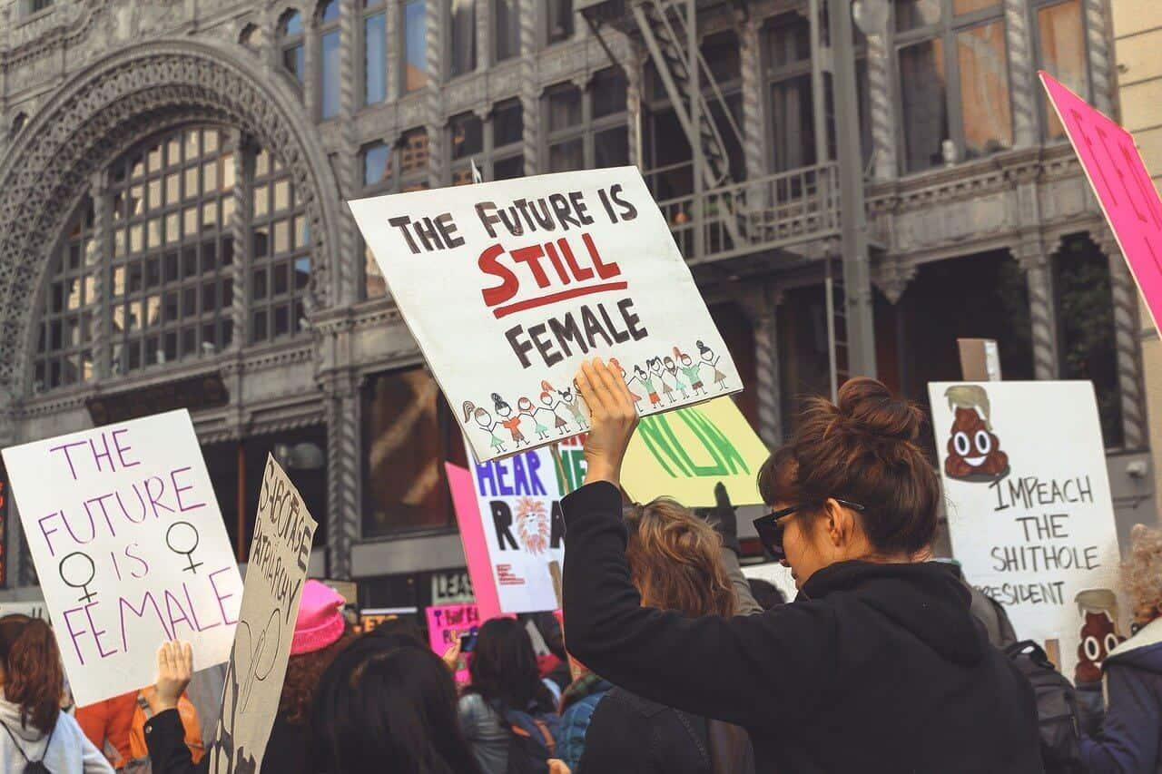 Frauen die für Feminismus demonstrieren und Schilder hoch halten